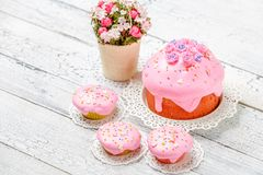 Traditional Easter cake and cupcakes. Traditional Easter cake with decorations and cupcakes on wooden table stock images