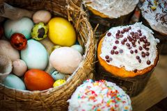 Traditional easter cake kulich Ukrainian with colored eggs in th. E wicker basket Royalty Free Stock Photo