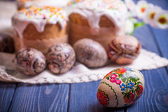 Traditional easter cake kulich Ukrainian Russian with colored eggs. On blue wooden background Stock Photos