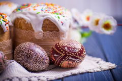 Traditional easter cake kulich Ukrainian Russian with colored eggs. On blue wooden background Royalty Free Stock Image