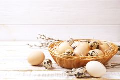 Traditional easter card template with pastel colors painted organic eggs in wicker basket with hay and decorative wildflowers. Royalty Free Stock Photos