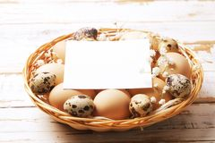 Traditional easter card template with unpainted mixed organic eggs in wicker basket with hay and decorative wildflowers. Royalty Free Stock Photography