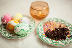 Traditional easter colorful eggs in a plate. A candle is burning nearby and a plate of sweets lies. Stock Images