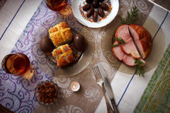 Traditional easter dinner set with sliced meat with herbs, chocolate eggs, easter cake and glasses of juice and a candle on colorf Royalty Free Stock Image