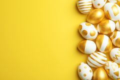 Traditional Easter eggs decorated with golden paint on color background, top view. Space for text stock photo