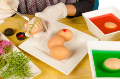 Traditional Easter eggs. Hands decorating Easter eggs leaves and flowers while dyeing some others Royalty Free Stock Image