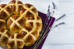 Easter hot cross buns with lavender flowers, chocolate eggs on napkin and wooden white table. Traditional Easter hot cross buns with lavender flowers, chocolate Stock Photography