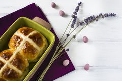 Easter hot cross buns with lavender flowers, chocolate eggs on napkin and wooden white table. Traditional Easter hot cross buns with lavender flowers, chocolate Stock Photo
