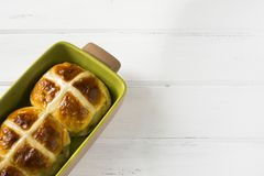 Easter hot cross buns on wooden white table. Traditional Easter hot cross buns on wooden white table. Easter baking Stock Photos