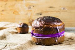 Traditional Easter panettone or russian kulich. On wooden background with flower Royalty Free Stock Photo