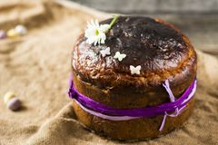 Traditional Easter panettone or russian kulich. On wooden background with flower Stock Images