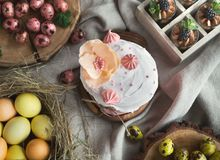 Traditional Easter sweet cake and coloured eggs. Traditional Easter sweet cake decorated with pink meringue and various coloured eggs on light background stock photos