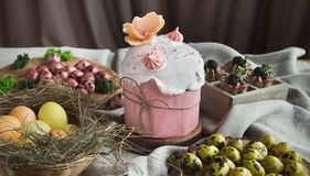 Traditional Easter sweet cake and coloured eggs. Traditional Easter sweet cake decorated with pink meringue and various coloured eggs on light background royalty free stock photo