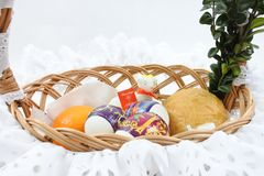 Traditional Easter wicker basket with white frill. Three Easter eggs decorated by shrink-wrap and white sugar lamb with Alleluja script, in a wicker basket with Stock Images