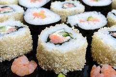 Traditional eastern dish with salmon sushi rolls on a black plate Royalty Free Stock Photo