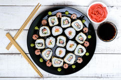 Traditional eastern dish with salmon sushi rolls on a black plate. Royalty Free Stock Photos