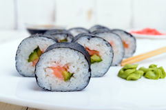 Traditional eastern dish with salmon sushi rolls on a white plate. Royalty Free Stock Photography