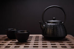 Traditional eastern teapot and teacups on wooden desk Royalty Free Stock Photography