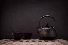 Traditional eastern teapot and teacups on wooden desk Stock Photo
