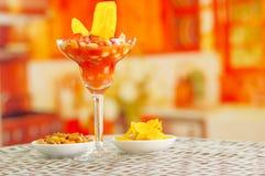 Traditional ecuadorian cold tomato based dish with chochos, onions and banana chips, elegant restaurant presentation.  Royalty Free Stock Image