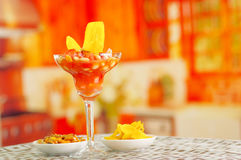 Traditional ecuadorian cold tomato based dish with chochos, onions and banana chips, elegant restaurant presentation.  Stock Photos