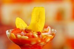 Traditional ecuadorian cold tomato based dish with chochos, onions and banana chips, elegant restaurant presentation.  Stock Image