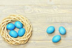 Traditional eggs painted in blue color inside woven wooden wreath royalty free stock image