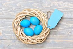 Traditional eggs painted in blue color inside woven wooden wreath royalty free stock photography