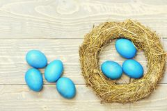 Traditional eggs painted in golden color inside woven straw wreath stock image