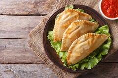 Traditional empanadas and sauce closeup. horizontal top view Stock Photos