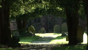 Traditional England with church land grave stones. Traditional scene of England looking through trees to gravestones stock video