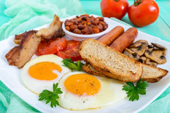 Traditional English breakfast: bacon, mushrooms, eggs, tomatoes, sausages, beans, toast on a white plate Royalty Free Stock Image