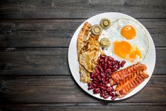 Traditional English Breakfast with fried eggs, sausages and beans stock photos