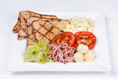 Traditional English breakfast with scrambled eggs. Tomatoes, potatoes, toast and fresh salad on a white background Stock Photography