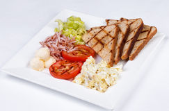 Traditional English breakfast with scrambled eggs. Tomatoes, potatoes, toast and fresh salad on a white background Stock Photos