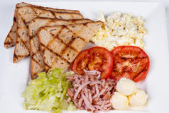 Traditional English breakfast with scrambled eggs. Tomatoes, potatoes, toast and fresh salad on a white background Stock Images