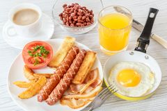 Traditional English breakfast with smoked sausages, bacon, tomato, toast and beans. Fried egg in a frying pan. Tea with milk. A gl Stock Images