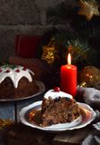Traditional english Christmas steamed pudding with winter berries, dried fruits, nut in festive setting with Xmas tree and burning. Candle. Fruit cake Stock Images