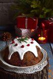 Traditional english Christmas steamed pudding with winter berries, dried fruits, nut in festive setting with Xmas tree and burning. Candle. Fruit cake Stock Image