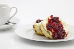 Traditional English cream tea. Of scones, clotted cream, strawberry jam and a cup of tea. These are served Devonshire style, with the jam on top Royalty Free Stock Photos