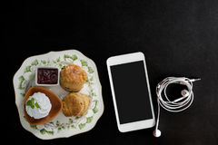 Traditional English cream tea of scones. Clotted cream, strawberry jam and smartphone on dark table Stock Image