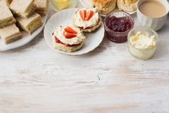 Traditional English cream teas, scones. English scones with butter, jam and cream, tea with milk, with selection of sandwiches on the back, on the white wooden Stock Image
