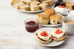 Traditional English cream teas, scones. English cream teas, scones with jam and cream, tea with milk, with sandwiches on the back, on the white wooden table Royalty Free Stock Photo