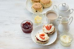 Traditional English cream teas, scones. With jam and cream, tea with milk, on the white wooden table, elevated view, selective focus, copy space for text Stock Image