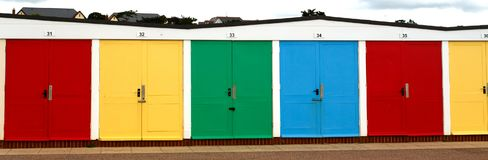 Traditional English multi-colored beach houses stand in a row on royalty free stock photography