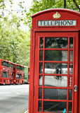 Traditional English Red Telephone Phone Box and Red Double Decker Buses London England Royalty Free Stock Image