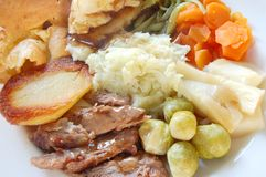 Traditional English roast dinner. Traditional English sunday roast lamb dinner with yorkshire pudding, fresh garden vegetables and gravy, macro Stock Photography