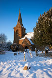 Traditional English village churchyard in snow Royalty Free Stock Images
