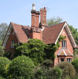 Traditional English Village Lodge. Traditional red brick English Village House with tall chimneys Stock Photo
