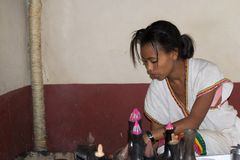 Traditional ethiopian coffee ceremony. Bahir Dar, Ethiopia - January 18, 2012: Cute ethiopian young woman in traditional clothings performing a traditional Royalty Free Stock Photo